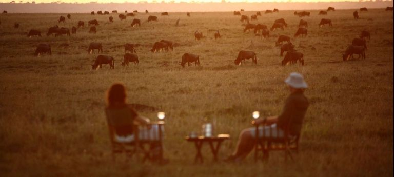 Enjoying a sundowner whilst watching the wildebeest migration.  | HerdTracker Masai Mara wildebeest migration safari